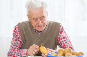 old man peeling potato